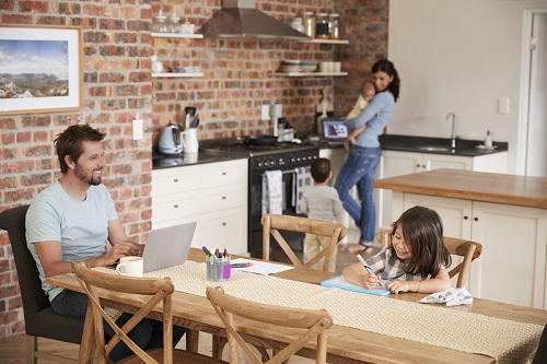 Busy Family Home With Father Working As Mother Prepares Meal